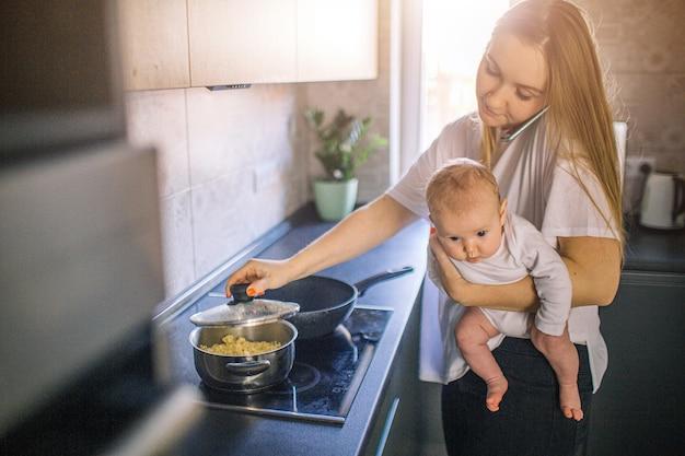 La madre tiene il suo bambino in braccio. e cucina in cucina. la mamma parla al telefono ed è molto impegnata. concetto di multifunzionalità. Foto Premium