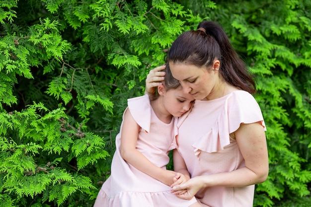 La madre abbraccia la figlia 5-6 anni seduti nel parco sull'erba, la conversazione madre-figlia, la madre si dispiace per il bambino, la relazione madre-figlio, la festa della mamma Foto Premium