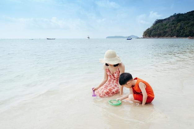 Una madre e un figlio sulla spiaggia all'aperto mare e cielo blu Foto Premium