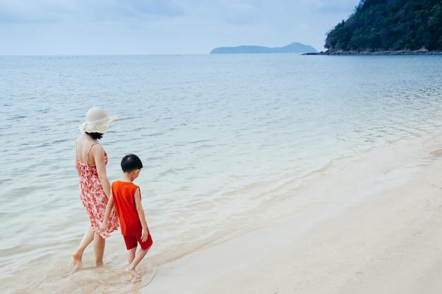 Una madre e figlio tenendo la mano e camminando sulla spiaggia e mare all'aperto al tramonto Foto Premium