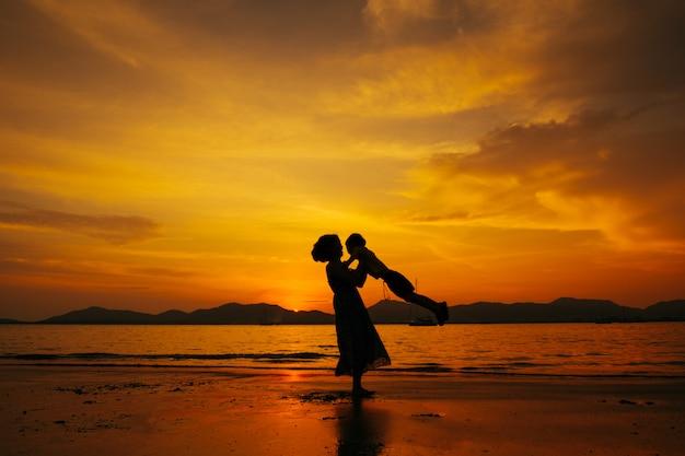 Una madre e un figlio dentro all'aperto al tramonto con lo spazio della copia Foto Premium