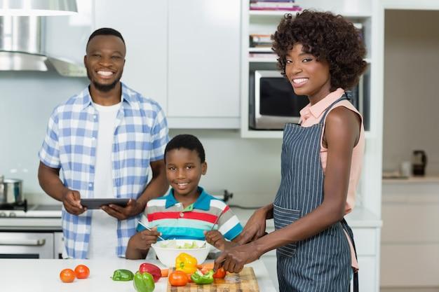 Madre e figlio che preparano insalata mentre padre che utilizza compressa digitale nella cucina a casa Foto Premium