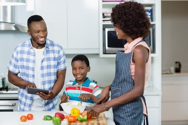 Madre e figlio che preparano insalata mentre padre che utilizza compressa digitale nella cucina Foto Premium