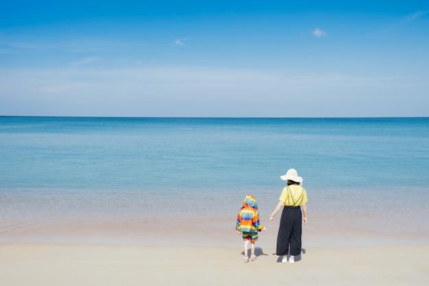 Una madre e un figlio che camminano sulla spiaggia e mare all'aperto mare e cielo blu Foto Premium