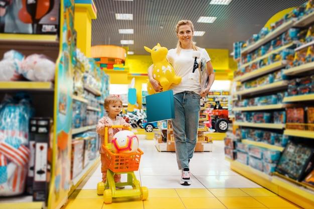 Madre con la sua bambina che compra un sacco di giocattoli nel negozio per bambini. Foto Premium