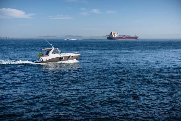 Imbarcazione a motore e un'autocisterna del carico nel mar nero Foto Premium