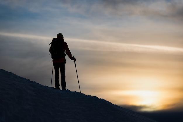 Uno sciatore di alpinismo osserva il tramonto Foto Premium