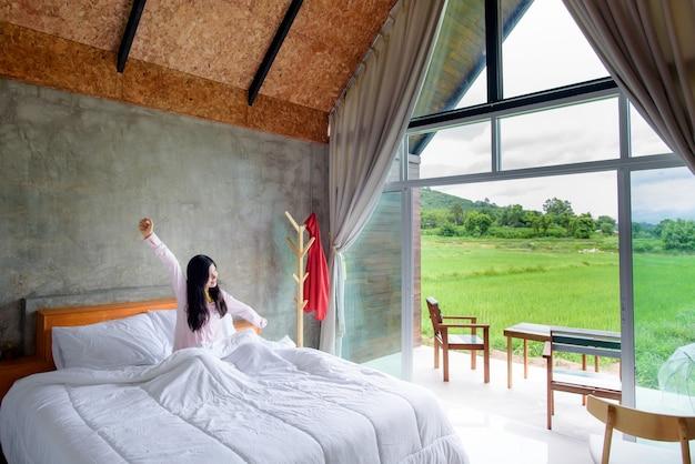 Mujer asiática acaba de despertar de la cama en una habitación con paisaje Foto Premium