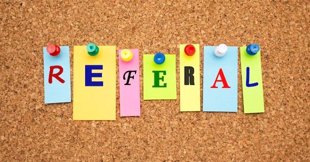Note multicolori con lettere appuntate su una bacheca di sughero. Foto Premium