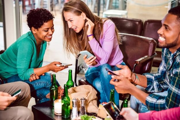Amici multirazziali che bevono birra e si divertono con i telefoni cellulari intelligenti al ristorante cocktail bar Foto Premium