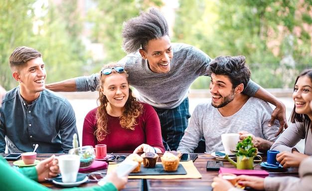 Amici multirazziali che bevono caffè al bar all'aperto Foto Premium