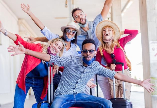 Gruppo multirazziale di amici alla stazione ferroviaria con i bagagli che indossa la maschera protettiva. Foto Premium