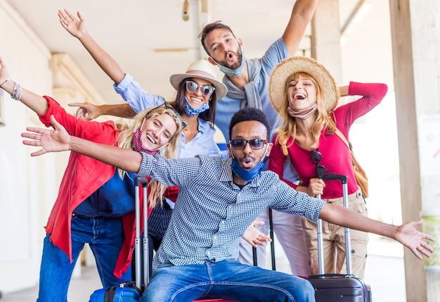 Gruppo multirazziale di amici alla stazione ferroviaria con i bagagli che indossa la maschera protettiva Foto Premium