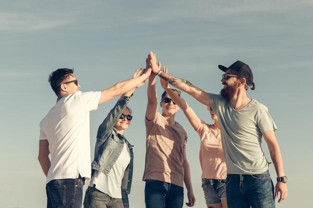 Gruppo multirazziale di amici con le mani sullo stack Foto Premium