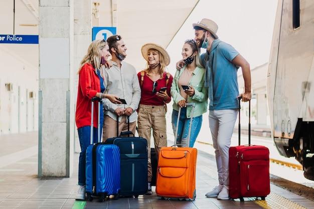 Gruppo multirazziale di persone che si divertono alla stazione ferroviaria. giovani amici che indossano la maschera per il viso durante le vacanze Foto Premium