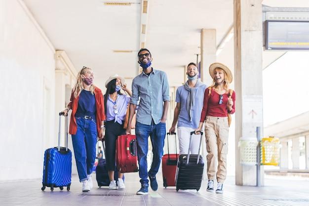 Gruppo multirazziale di giovani che indossano la maschera per il viso a piedi alla stazione ferroviaria in vacanza. nuovo normale concetto di viaggio e vacanza. Foto Premium
