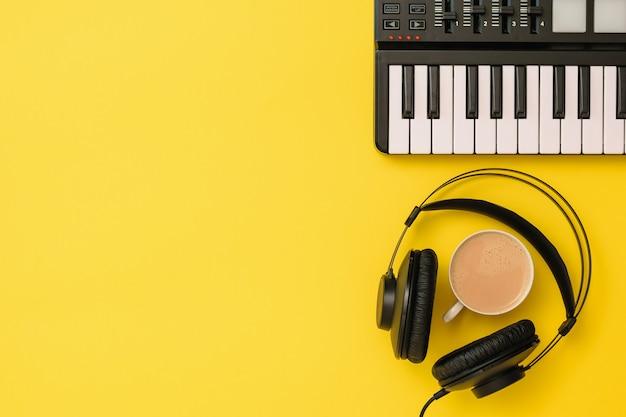 Mixer musicale e cuffie nere e caffè su sfondo giallo. attrezzatura per la registrazione di brani musicali. la vista dall'alto. lay piatto. Foto Premium