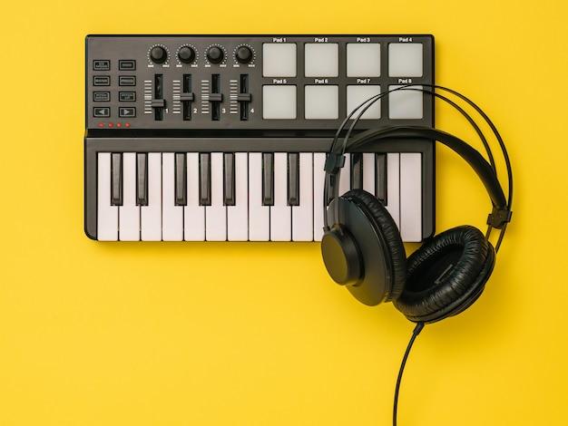 Mixer musicale e cuffie nere su sfondo giallo. attrezzatura per la registrazione di brani musicali. la vista dall'alto. lay piatto. Foto Premium