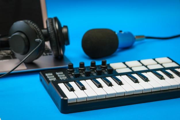Mixer musicale, laptop e microfono blu con fili sulla superficie blu. attrezzatura per la registrazione di brani musicali. Foto Premium