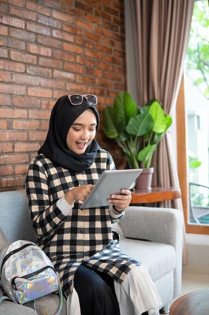 Donna musulmana a casa facendo uso della compressa Foto Premium