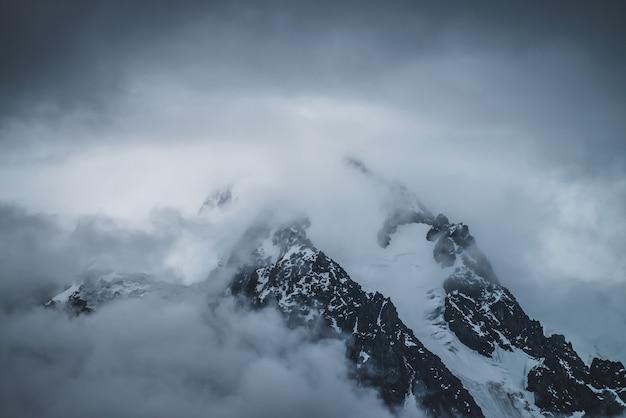 Misterioso scenario alpino drammatico con montagne innevate Foto Premium