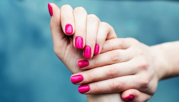 Design delle unghie. mani con manicure estate rosa su sfondo grigio. primo piano di mani femminili. nail art. Foto Premium