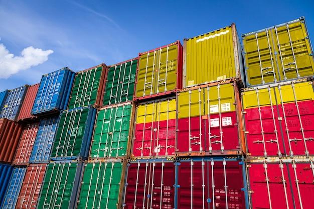 Bandiera nazionale del benin su un gran numero di contenitori metallici per lo stoccaggio di merci accatastate in file Foto Premium