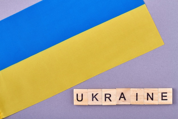 Bandiera nazionale dell'ucraina. colori blu e gialli sul banner. blocchi di legno di lettere isolati su sfondo viola. Foto Premium