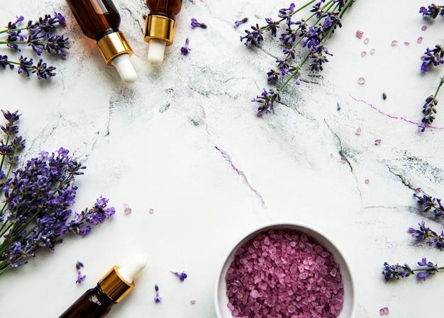 Cosmetico alle erbe naturali con lavanda, flatlay su sfondo di marmo bianco, vista dall'alto Foto Premium