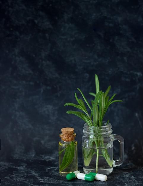 Olio essenziale di rosmarino naturale, foglie fresche e capsule a base di erbe per bellezza e spa su sfondo scuro con spazio di copia Foto Premium