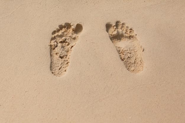 Consistenza naturale e sfondo. orme nella sabbia gialla sulla spiaggia Foto Premium
