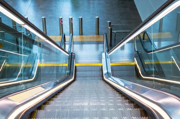 L'escavatore in metallo illuminato al neon con le scale di corrimano in gomma visualizza la discesa fino al pavimento. Foto Premium