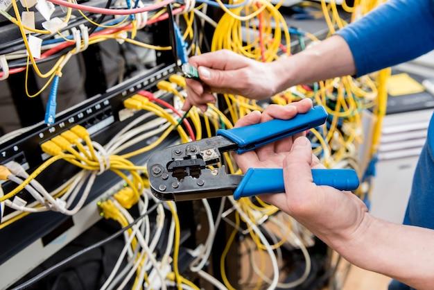 Ingegnere di rete che lavora nella sala server. collegamento dei cavi di rete agli switch Foto Premium