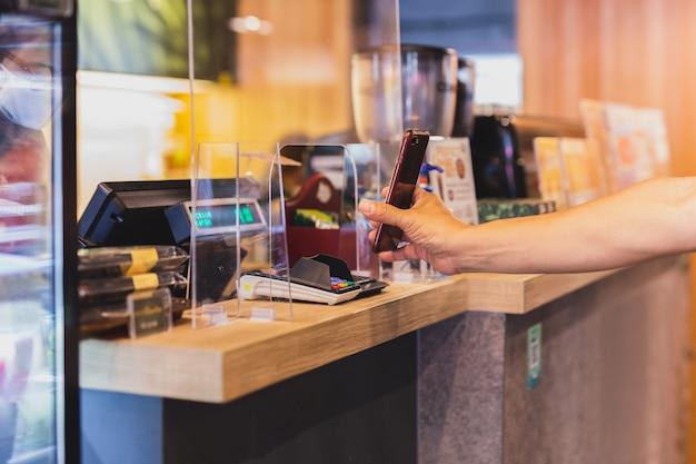 Nuovo cliente nomar che paga la fattura dal telefono cellulare con il personale behid la partizione di plastica in caffè. Foto Premium