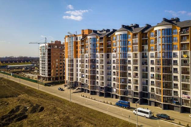 Le nuove costruzioni di appartamento alte e le automobili e le case parcheggiate del sobborgo sul cielo blu copiano il fondo dello spazio. Foto Premium