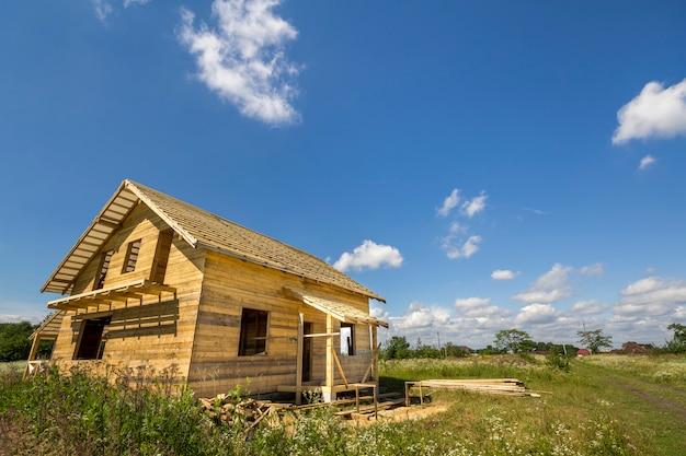 Nuovo cottage tradizionale ecologico di legno dei materiali naturali del legname con il tetto ripido in costruzione in vicinanza verde sullo spazio della copia del cielo blu. concetto di costruzione professionale. Foto Premium