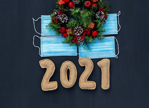 Il nuovo anno nel contesto del coronavirus ha lavorato a maglia i numeri 2021 sulla mascherina medica sulla lavagna Foto Premium