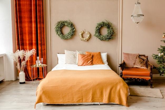 Interior design di capodanno della bella camera da letto nei toni del beige con l'albero di natale Foto Premium