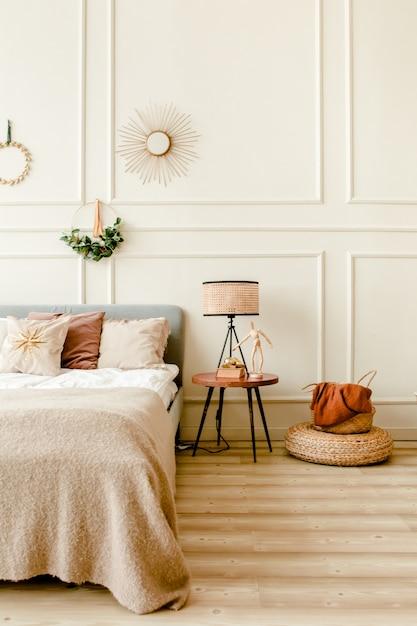 Interior design di capodanno della bella camera da letto nei toni del beige con rami di abete ghirlanda Foto Premium