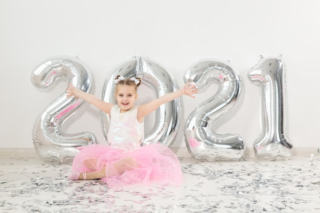 Anno nuovo, vacanze e concetto di celebrazione - bambina seduta vicino con palloncini numeri Foto Premium