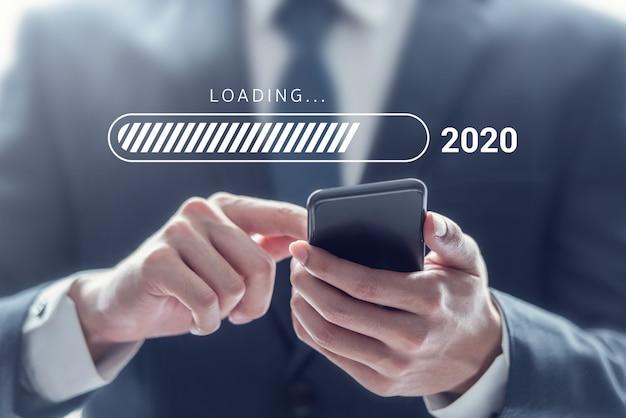 Anno nuovo caricamento 2020, uomo d'affari che utilizza smartphone mobile. Foto Premium