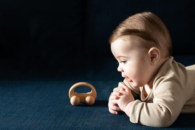 Il ragazzo del bambino appena nato in tuta beige gioca con la vista laterale del giocattolo di legno Foto Premium