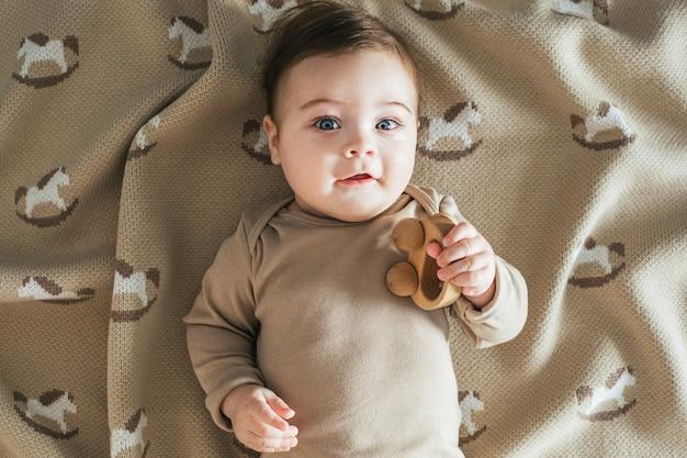 Il neonato in tuta beige gioca con la vista dall'alto del giocattolo di legno Foto Premium