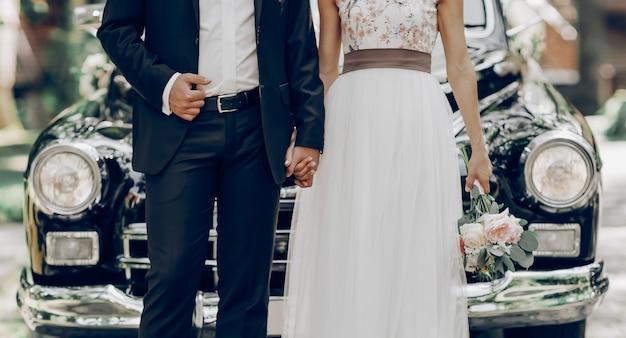 Coppia di sposi di fronte a un'auto classica nera Foto Premium