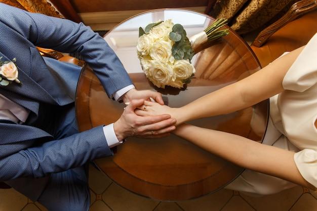 Sposi che si tengono per mano vicino al bouquet da sposa Foto Premium