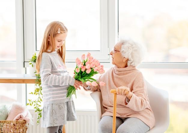 Bella bambina che presenta bouquet a sua nonna nella stanza leggera Foto Premium