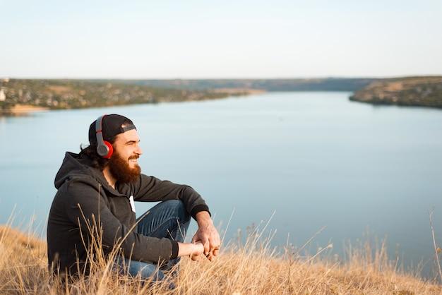 Bel giovane barbuto seduto sul campo ascoltando la musica e sorridendo e guardando lontano Foto Premium