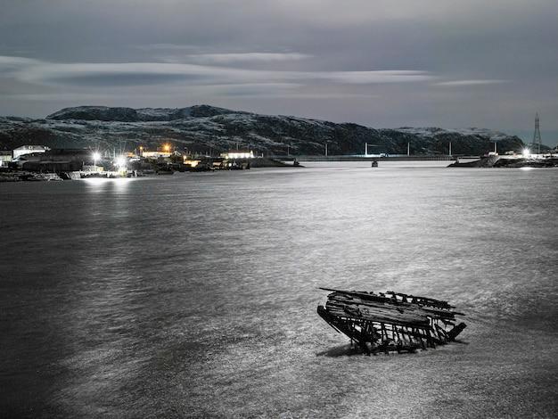 Vista notturna del cimitero delle navi, antico villaggio di pescatori sulla riva del mare di barents, la penisola di kola Foto Premium