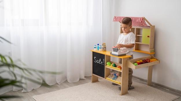 Bambino non binario che gioca al chiuso con lo spazio della copia Foto Premium