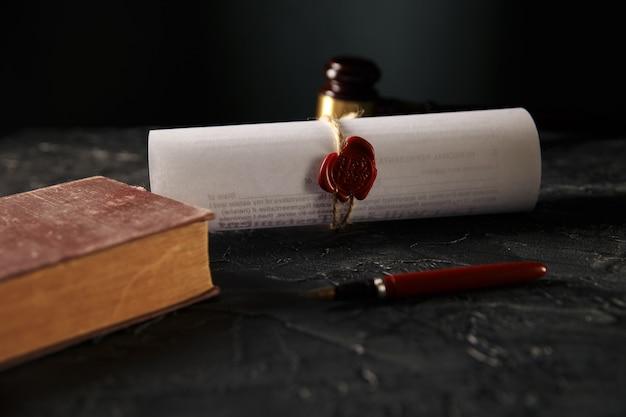 Notaio e nozione di diritto. timbro con libro e penna sul tavolo. martelletto di legno dietro. Foto Premium